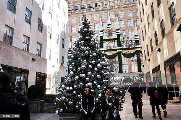 People have their picture taken with a Christmas tree on Fifth Avenue in New York on November 24 2015 AFP PHOTO/JEWEL SAMAD / AFP / JEWEL SAMAD