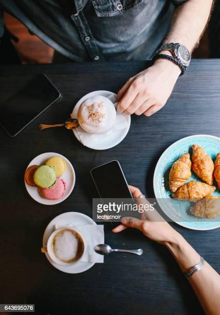 Personas que tienen un café y dulces en la cafetería