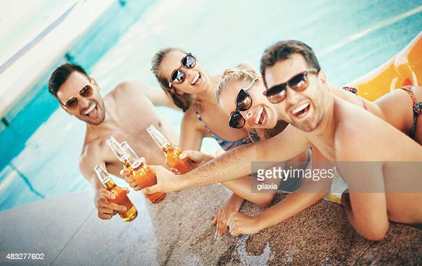 People having beers at poolside.