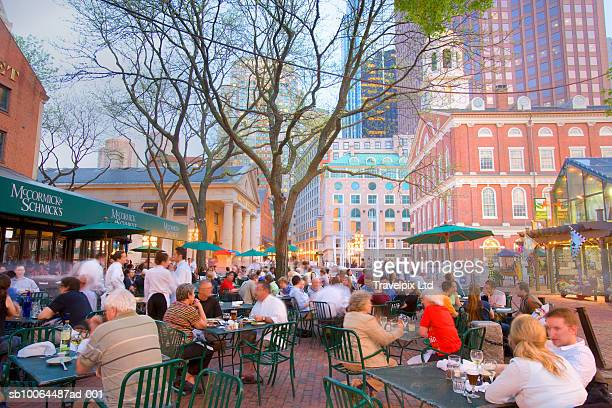 People having breakfast at pavement cafT, Faneuil hall in background