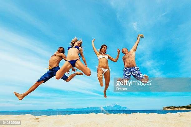 People having fun at beach in summer, jumping on sand