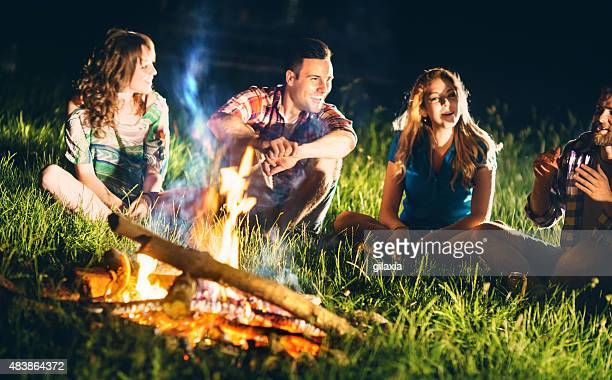 People having fun by campfire.