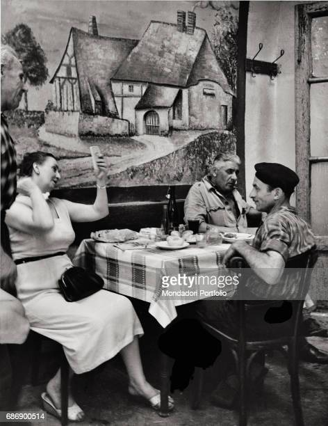 People having fun in Trattoria La Pergola This picture is taken from the monography 'Mario De Biasi Il mio sogno Š qui' curated by Enrica Vigan•...