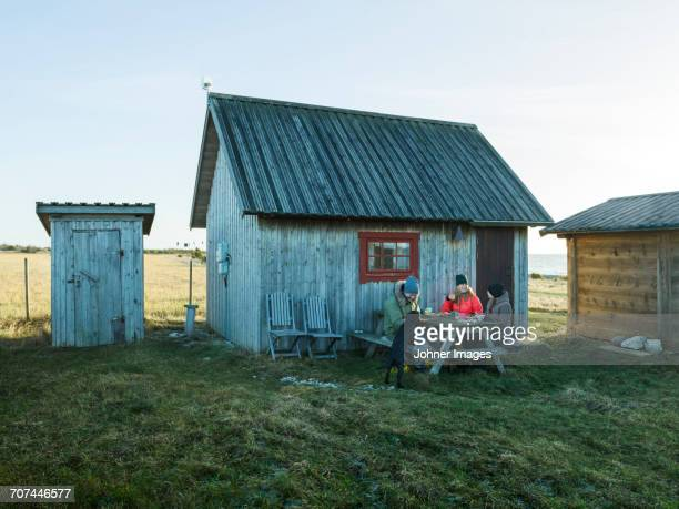 People having meal in front of wooden house