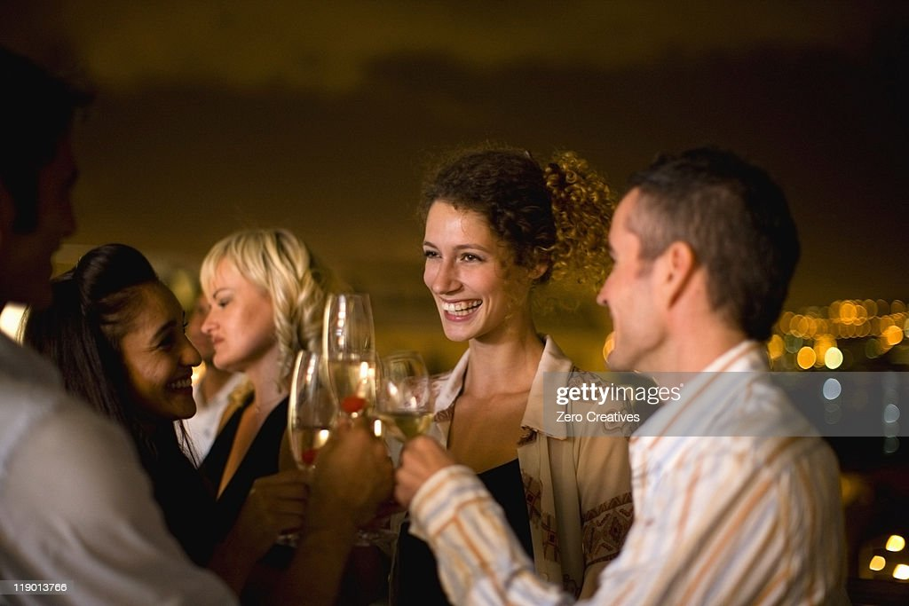 People having wine on terrace at night