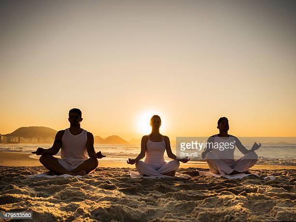 People having Yoga class on the beach at sunset.
