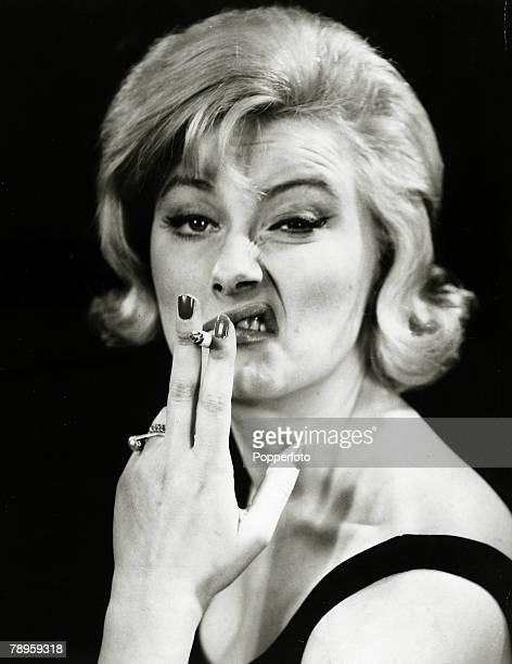 circa 1960's A woman pulls a 'sneering' face whilst smoking a cigarette