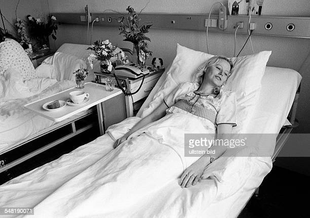 people health young woman lies in a sickbed of a hospital aged 30 to 40 years Elisabeth