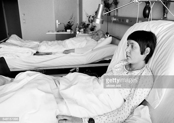 people health young woman lies in a sickbed of a hospital beside her lies a older woman aged 25 to 30 years aged 70 to 80 years Monika