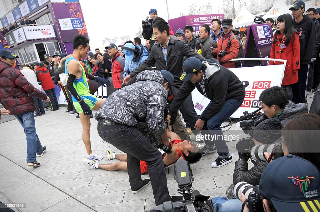 People help a particpant after he fell to the ground after running in the Beijing Marathon in the Chinese capital on November 25, 2012. A total of 30,000 runners took part in the race. AFP PHOTO / WANG ZHAO