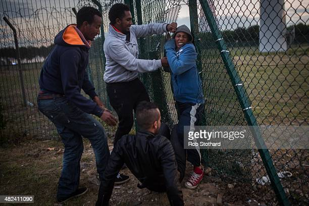People help a young man squeeze through a gap in a fence near the Eurotunnel terminal in Coquelles on July 30 2015 in Calais France Hundreds of...