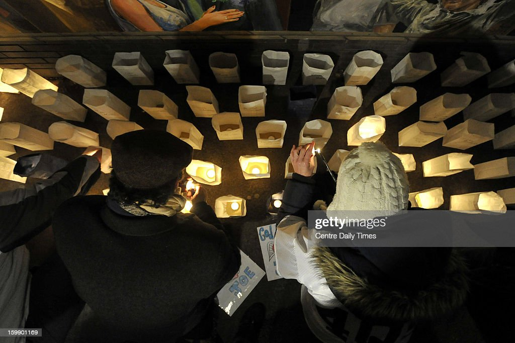 People help light some of the 409 luminaries placed for a candlelight vigil marking one year since Joe Paterno's death at the Inspiration Mural in State College, Pennsylvania, on Tuesday, January 22, 2013.