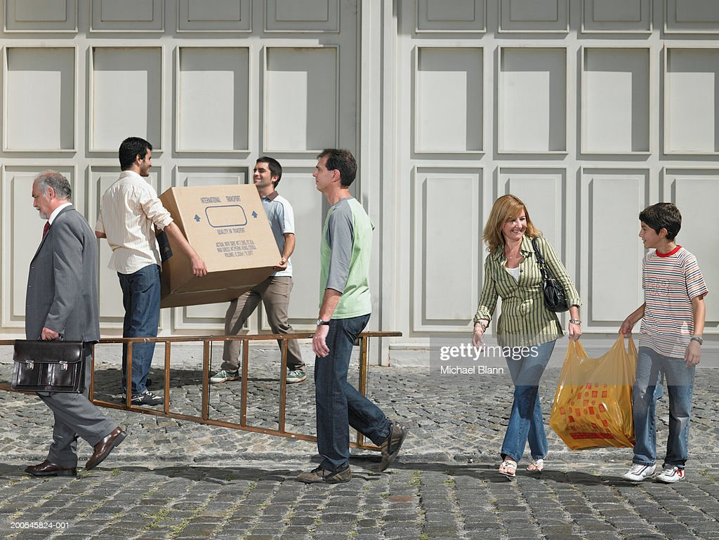 People helping each other carry items in street : Stock Photo
