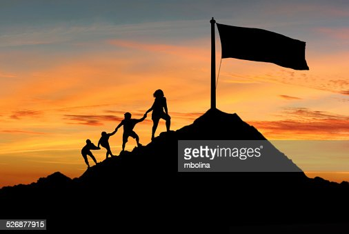 People helping each other to reach top of the mounting : Stock Photo