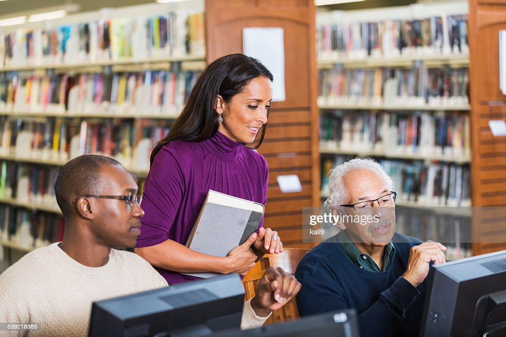 People helping senior man use computer in library