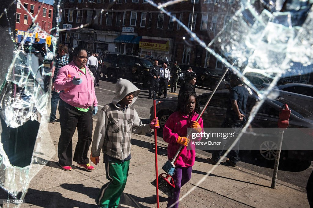 People helping to clean up debris caused by rioting yesterday after the funeral of Freddie Gray are seen in the reflection of a partially destroyed...