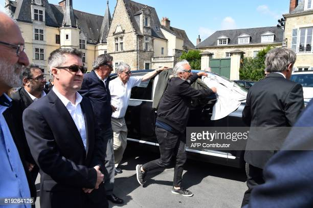People hide the relatives of French judge JeanMichel Lambert as they leave in the hearst at the end of his funeral at the SaintJulien Cathedral in Le...