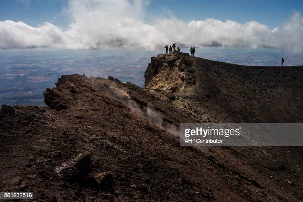 TOPSHOT People hike on September 21 2017 on the Mount Etna volcano on the Italian island of Sicily / AFP PHOTO / Guillaume BAPTISTE