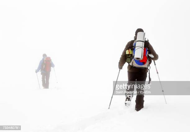 People Hiking In Snow