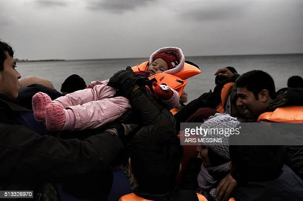 People hold a baby as migrants and refugees arrive on the Greek island of Lesbos while crossing the Aegean Sea from Turkey on March 2 in Mytilene The...