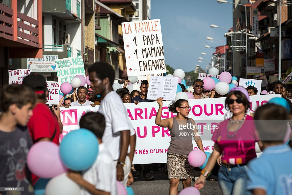 People hold a banner and placards during a protest against same-sex marriage, in Cayenne, in French Guiana, on January 12, 2013. Tens of thousands are set to march in Paris, on January 13, 2013 to denounce government plans to legalise same-sex marriage and adoption which have angered many Catholics and Muslims, France's two main faiths. The French parliament is to debate the bill -- one of the key electoral pledges of Socialist President at the end of this month.