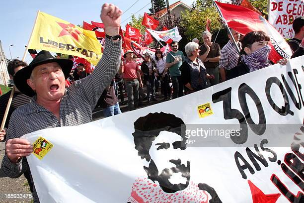 People hold a banner and shout slogans as they take part in a protest calling for the liberation of Lebanese activist Georges Ibrahim Abdallah in...