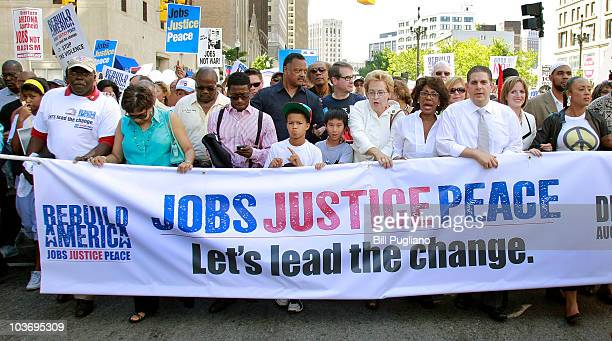 People hold a banner and signs as they participate in a 'Rebuild AmericaJobs Justice and Peace' march in the downtown area August 28 2010 in Detroit...