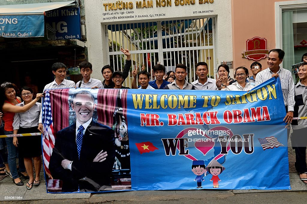 People hold a banner as they line up the streets to catch a glimpse of US President Barack Obama on his way to the airport at the end of two-day visit to Ho Chi Minh City on May 25, 2016. Obama fielded questions on May 25 on everything from rap and weed smoking to leadership and his good looks at a lively town hall-style meeting with young Vietnamese, who say the US leader is a far cry from their staid Communist rulers. / AFP / CHRISTOPHE
