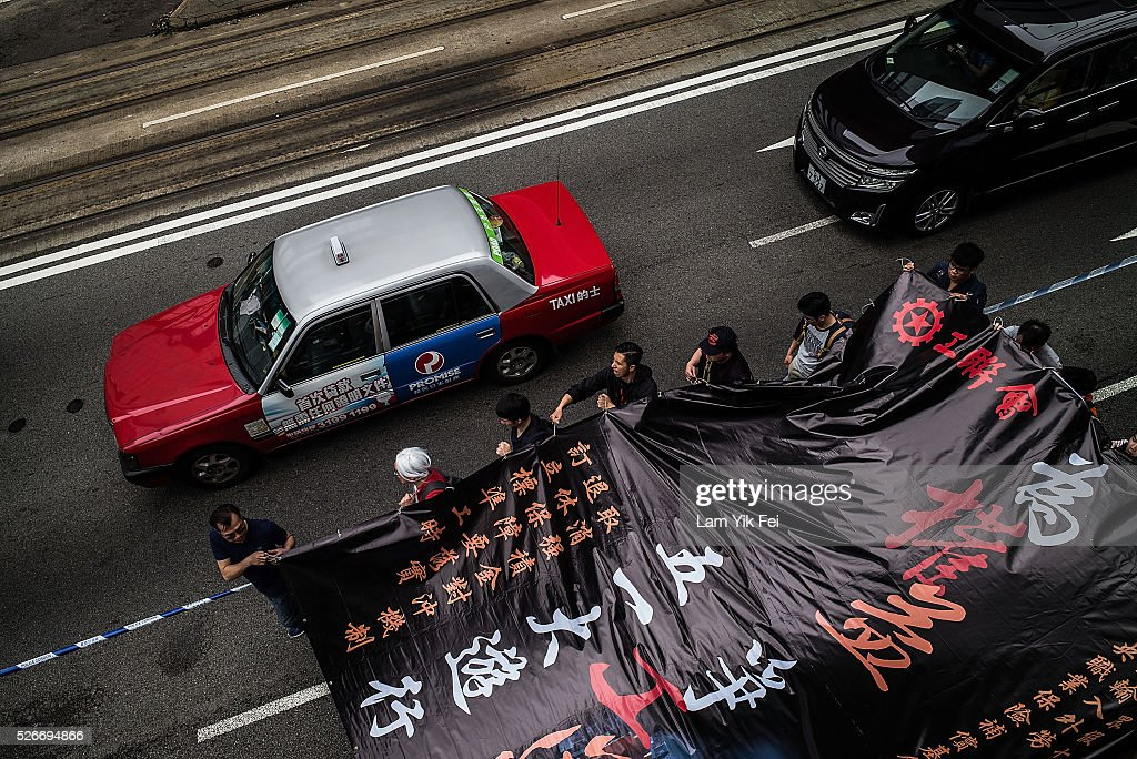 People hold a banner as they take part in a Labour Day rally on May 1, 2016 in Hong Kong, Hong Kong. Hundreds gathered in Hong Kong on Labor Day, demanding better workers' rights while voicing out their resentment against mainland travellers in Hong Kong.