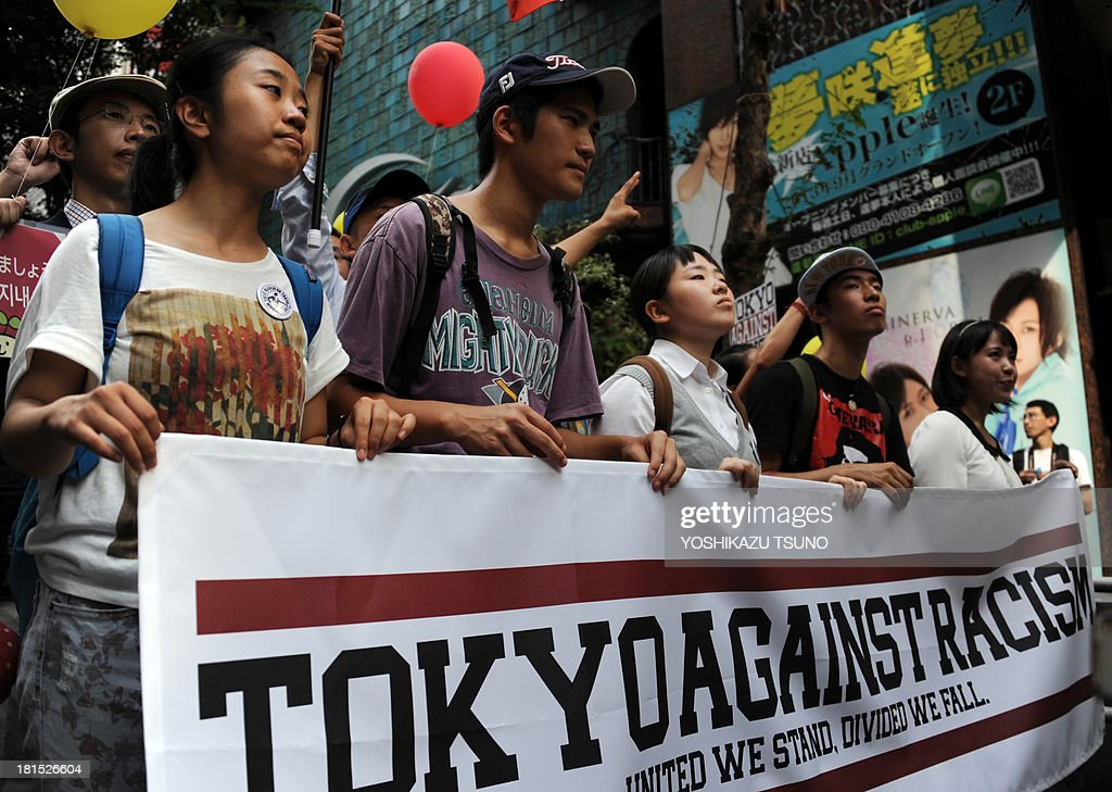 People hold a banner at an anti-racism demonstration in Tokyo on September 22, 2013. Some 2,000 people took part in an anti-discrimination rally to commemorate the 50th anniversary of the March on Washington and Martin Luther King Jr.'s 'I have a dream' speech on August 28, 1963. AFP PHOTO / Yoshikazu TSUNO