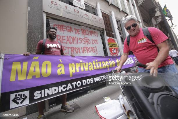 People hold a banner during a demonstration against employee layoffs and the expansion of the privatization of subway lines in front of the subway...