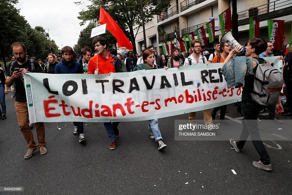 People hold a banner during a demonstration against the series of controversial labour reforms on June 28, 2016 in Paris. / AFP / Thomas SAMSON