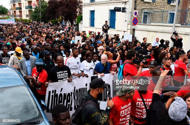 People hold a banner during a march in memory of Adama Traore who died during his arrest by the police in July 2016 on July 22 2017 in...