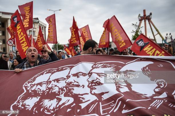 TOPSHOT People hold a banner picturing Communist figures including German philosopher and communist theoretician Karl Marx German philosopher and...