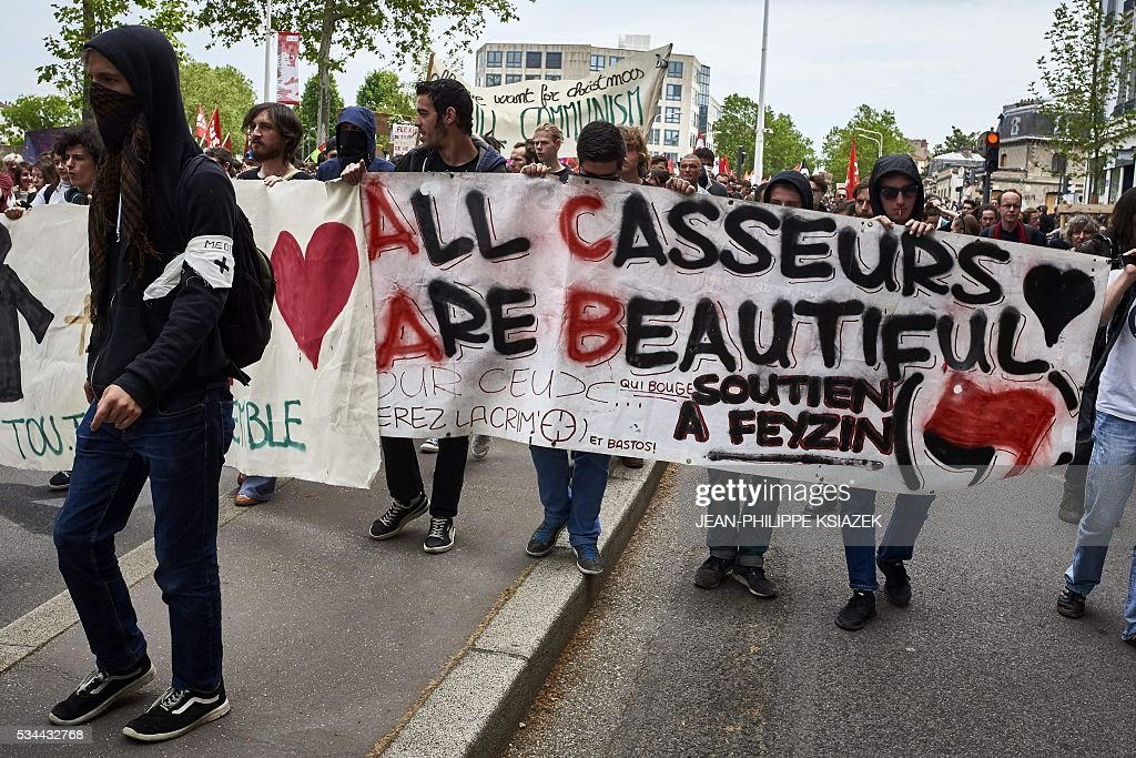People hold a banner reading 'All Casseurs (troublemarkers) Are Beautiful, solidarity with Feyzin' during a demonstration against the government's planned labour reform, on May 26, 2016 in Lyon, central eastern France. The French government's labour market proposals, which are designed to make it easier for companies to hire and fire, have sparked a series of nationwide protests and strikes over the past three months. Masked youths clashed with police in Paris and striking workers blockaded refineries and nuclear power stations on May 26, 2016 as an escalating wave of industrial action against labour reforms rocked France. KSIAZEK