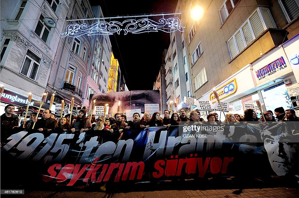 People hold a banner reading ('From 1915 to Hrant, genocide continues') during a march in memory of slain journalist <a gi-track='captionPersonalityLinkClicked' href=/galleries/search?phrase=Hrant+Dink&family=editorial&specificpeople=741548 ng-click='$event.stopPropagation()'>Hrant Dink</a>, on Istiklal avenue in Istanbul on January 19, 2015. Turkish riot police were out in force as large crowds massed in Istanbul to demand justice for a prominent Turkish Armenian journalist murdered eight years ago. <a gi-track='captionPersonalityLinkClicked' href=/galleries/search?phrase=Hrant+Dink&family=editorial&specificpeople=741548 ng-click='$event.stopPropagation()'>Hrant Dink</a>, one of the most prominent voices of Turkey's shrinking Armenian community, was killed by a gunman on January 19, 2007. The 52-year-old Dink, a prominent member of Turkey's tiny Armenian community, campaigned for reconciliation but was hated by Turkish nationalists for calling the World War I massacres of Armenians a genocide. AFP PHOTO /OZAN KOSE