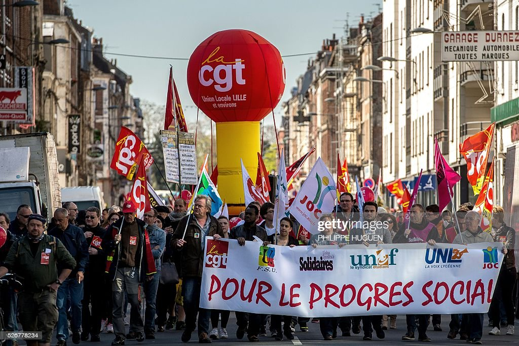 People hold a banner reading 'For social progress' as they march in the streets of Lille during a May Day rally on May 1, 2016. / AFP / PHILIPPE
