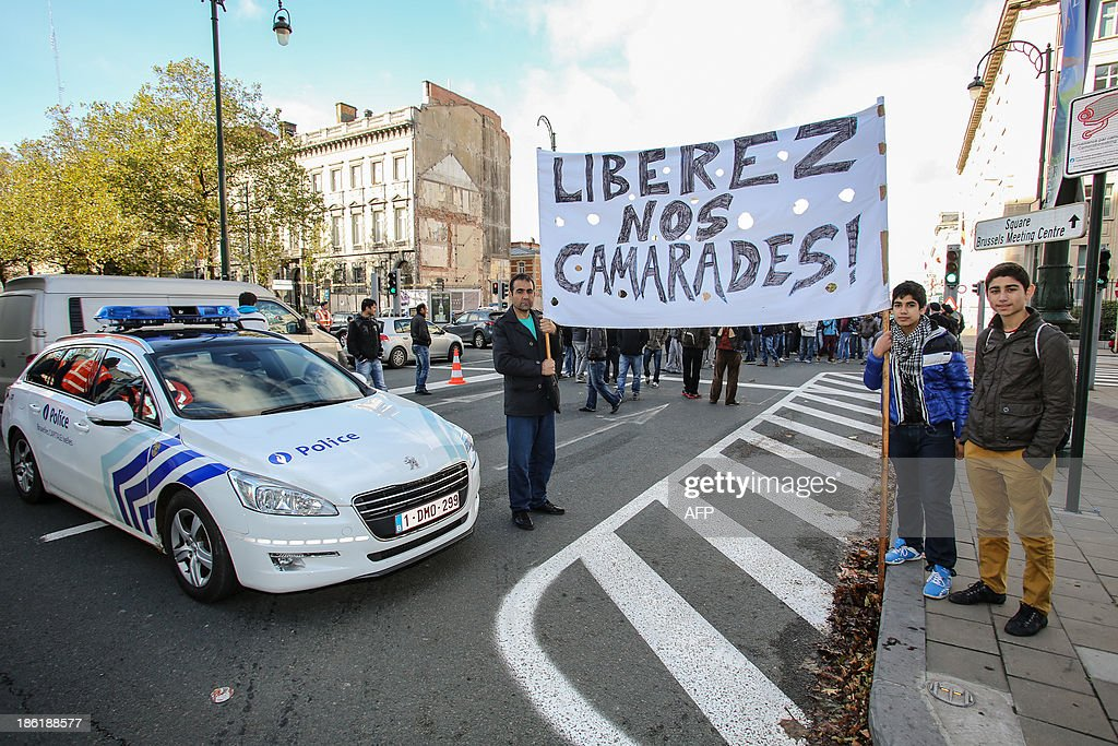 People hold a banner reading 'Free our comrades' during a demonstration of Afghan refugees on the Wetstraat - rue de la Loi in Brussels on October 29, 2013.