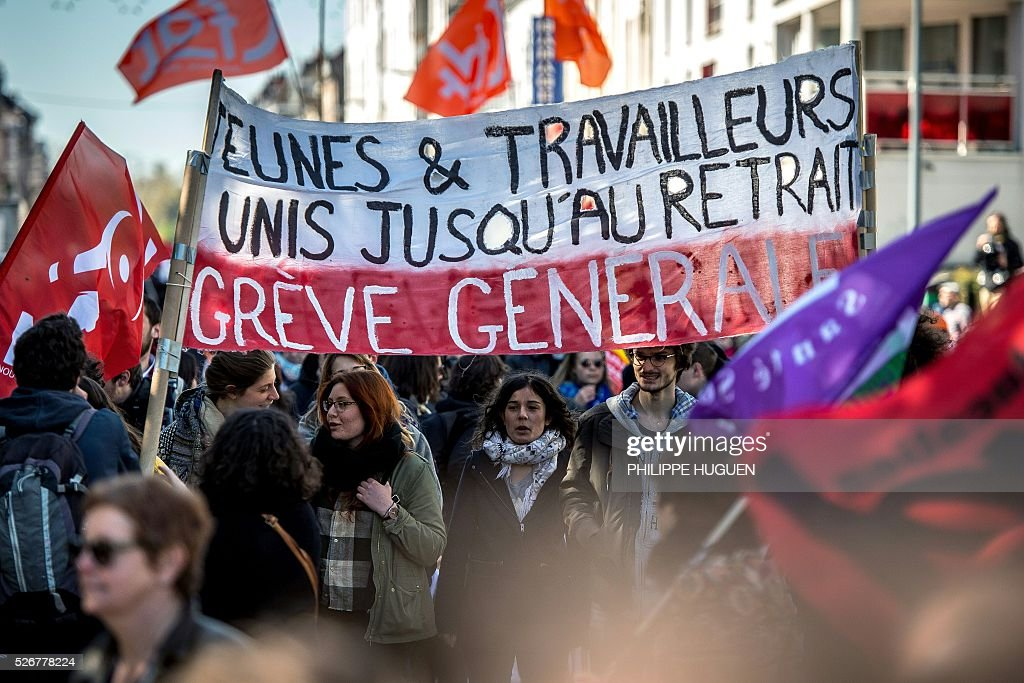 People hold a banner reading 'General strike, youths and workers united until retiremente' as they march in the streets of Lille during a May Day rally on May 1, 2016. / AFP / PHILIPPE