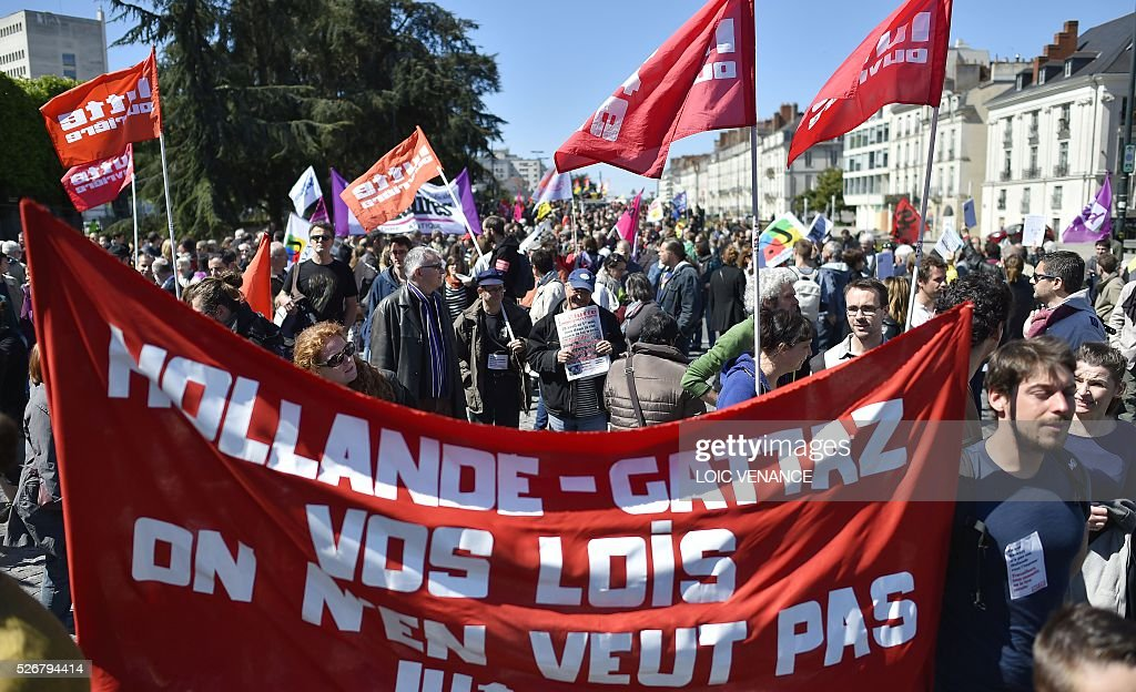 People hold a banner reading 'Hollande-Gattaz (head of French employers' association MEDEF) we don't want your laws' as they take part in the traditional May Day rally in Nantes, western France, on May 1, 2016. / AFP / LOIC