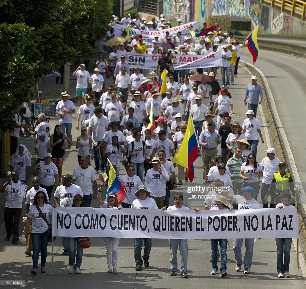 People hold a banner reading 'I don't believe the story they want power not peace' during a march against the current peace talks with FARC rebels in...