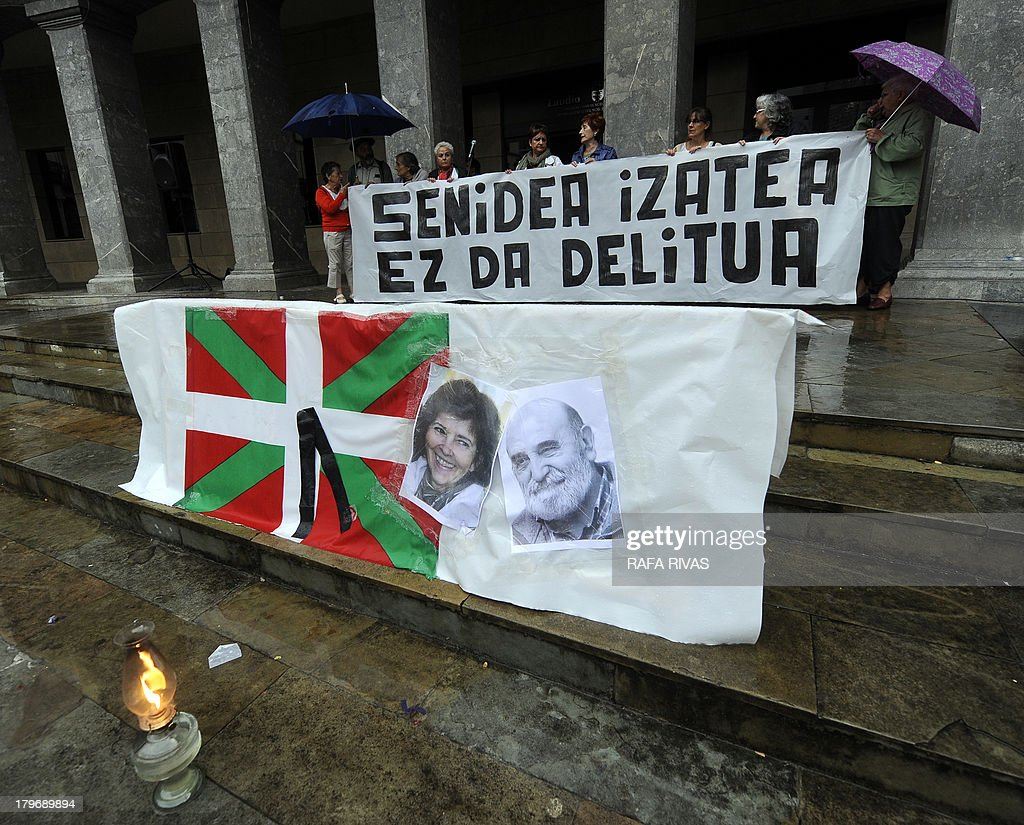 People hold a banner reading in Basque 'Being a relative (of Basque prisoners) is not a crime' as they pay tribute to the late wife of Batasuna's imprisoned member Pablo Gorostiaga, Judith Uriarte, who died on September 2, during a demonstration in favour of ETA imprisoned members in the Northern Spanish Basque village of Llodio on September 6, 2013. Hundreds of ETA members are in prison in Spain and France, including many of its leaders who have been arrested over recent years. ETA demands that its imprisoned members be moved to prisons closer to home. AFP PHOTO / RAFA RIVAS