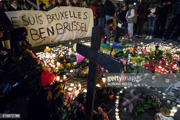 People hold a banner reading in French and Flamish 'I AM BRUSSELS' as they gather around floral tributes candles belgian flags and notes in front of...
