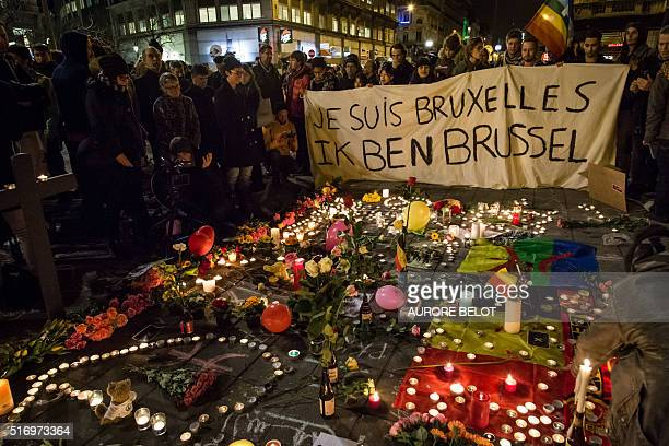 TOPSHOT People hold a banner reading in French and Flamish 'I AM BRUSSELS' as they gather around floral tributes candles belgian and peace flags and...