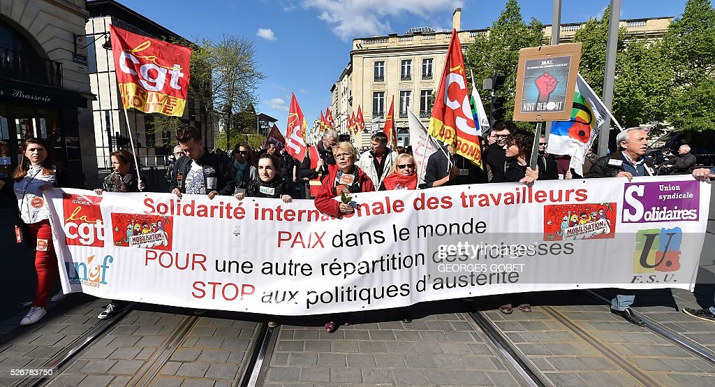 People hold a banner reading 'International solidarity of workers : Peace in the world, in favour of a different distribution of wealth, stop to austerity policies' as they demonstrate in the streets of Bordeaux during the traditional May Day rally on May 1, 2016. / AFP / GEORGES