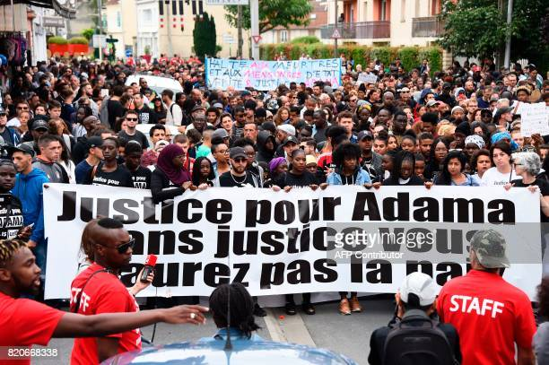 People hold a banner reading 'Justice for Adama without justice you won't have peace' during a march in memory of Adama Traore who died during his...