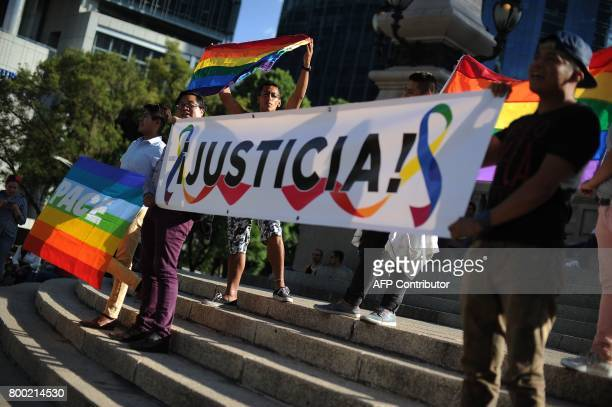 People hold a banner reading 'Justice' in a protest against violence targeting the LGBT community the day before the Gay Pride Parade in Mexico City...