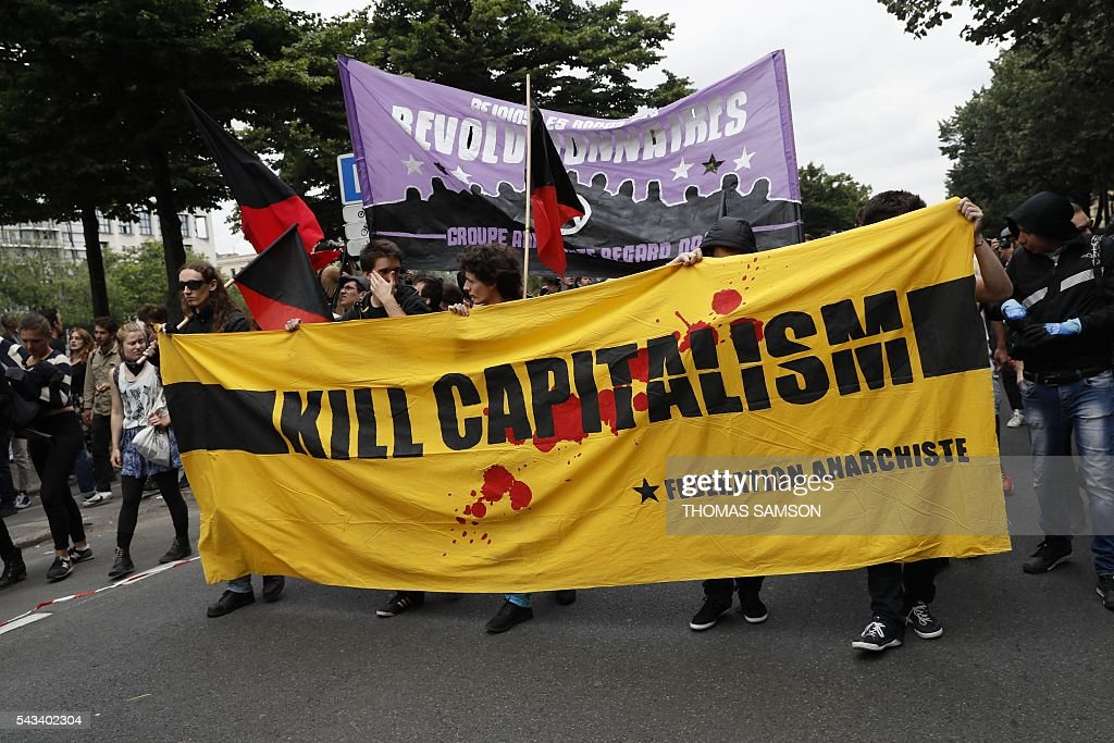 People hold a banner reading 'Kill capitalism' during a demonstration against the series of controversial labour reforms on June 28, 2016 in Paris. / AFP / Thomas SAMSON