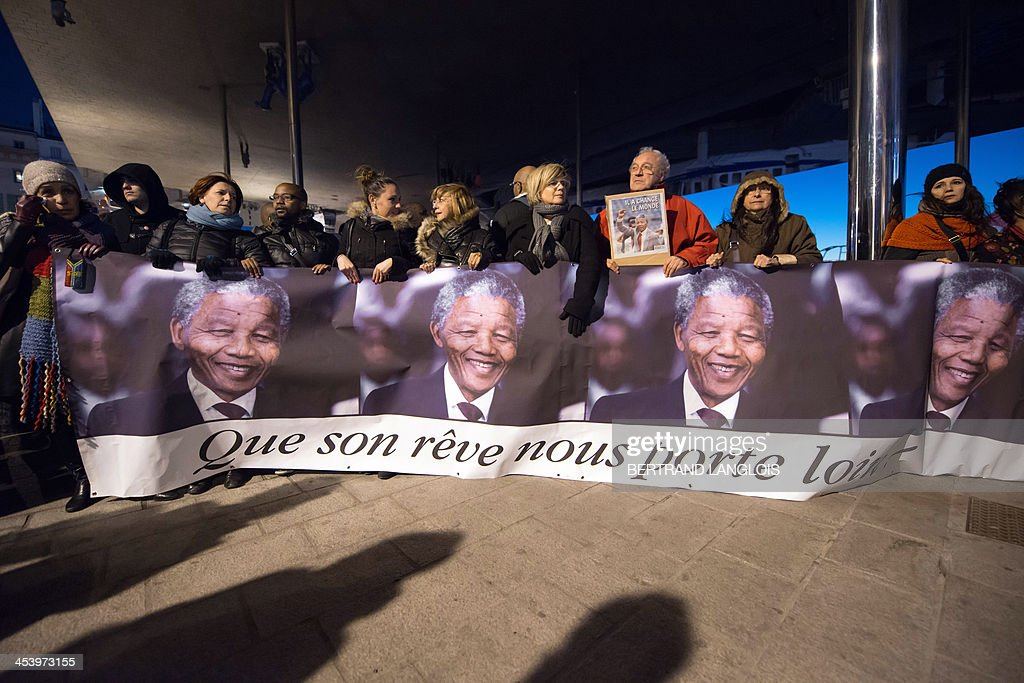 People hold a banner reading 'Let his dream take us far!' as they pay tribute to late South African former president Nelson Mandela on the Vieux-Port in Marseille, southern France, on December 6, 2013, a day after his death. The revered icon of the anti-apartheid struggle in South Africa and one of the towering political figures of the 20th century died in Johannesburg on December 5, 2013 at age 95. Mandela, who was elected South Africa's first black president after spending nearly three decades in prison, had been receiving treatment for a lung infection at his Johannesburg home since September, after three months in hospital in a critical state. AFP PHOTO / BERTRAND LANGLOIS