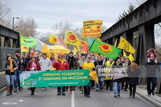People hold a banner reading 'Let's close Fessenheim and get out of the nuclear'' as they cross a bridge over the Rhine river at the FrancoGerman...